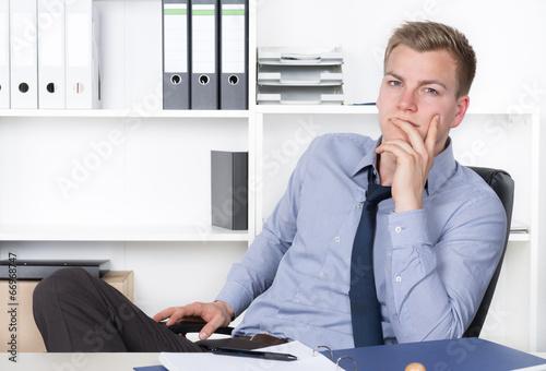 canvas print picture Junger nachdenklicher Mann sitzt am Schreibtisch im Büro