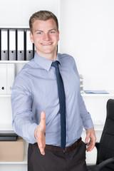 Lächelnder Mann reicht die Hand zur Begrüßung