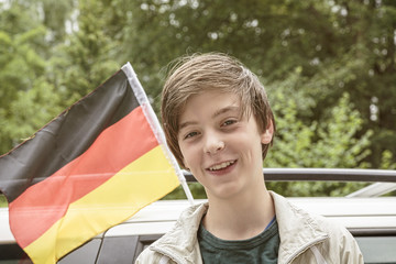 smiling male teenager in front of a german flag