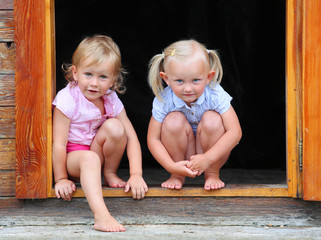 Funny kids in the doorway to an rural house.