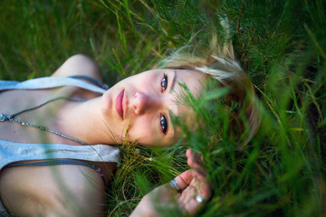 Girl lying in the grass at sunset