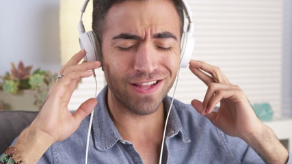 Mexican guy singing along to music with headphones