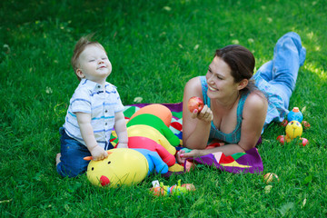 happy mother woman and baby boy kid child on background of grass