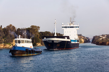 Cargo ship and tugboat crossing Corinth canal, Greece