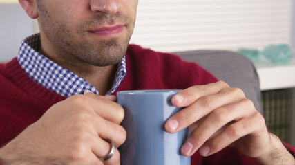 Closeup on a Hispanic man drinking his morning coffee