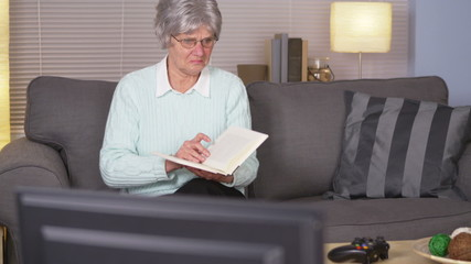 Elderly woman chooses videogames over reading a book