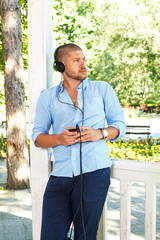 Handsome guy listening to music via smartphone