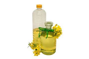 glass and plastic bottle of rape seed oil with rape flowers