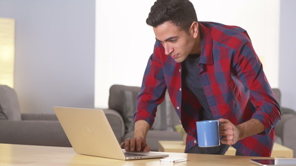 Mexican man working on laptop and drinking coffee