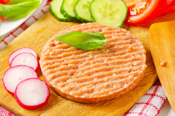 Raw minced meat patty and vegetables