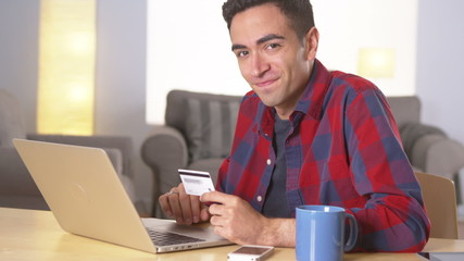 Hispanic man smiling with credit card