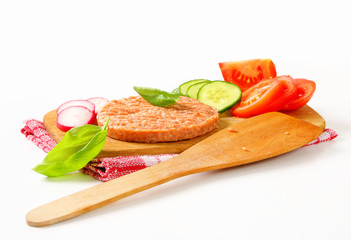 Raw burger patty and sliced vegetables