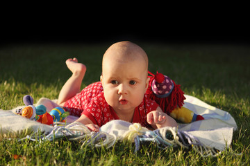 Adorable baby girl lying on green summer grass