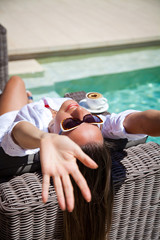 Happy young woman laying on chaise-longue poolside