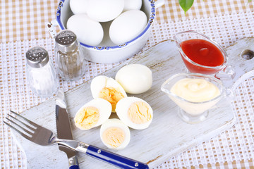 Boiled eggs on wooden board on tablecloth