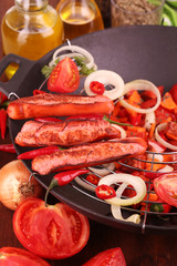 Delicious sausages with vegetables in wok close-up
