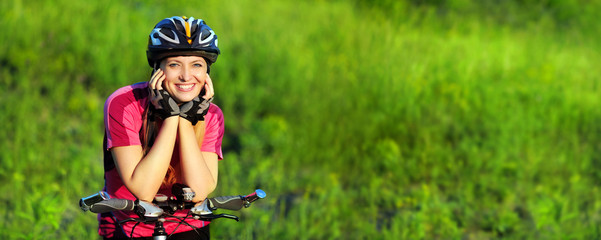 beautiful bicyclist woman on green landscape background