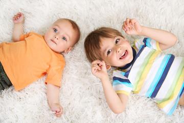 Cute little boys lying on carpet