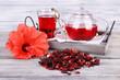 Leinwanddruck Bild - Hibiscus tea in glass teapot and flower