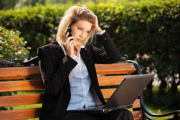 Young business woman with laptop calling on the cell phone