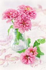 beautiful pink flowers in a glass vase on a beautiful tablecloth