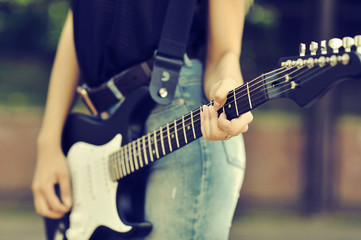 Close up photo of guitar female player