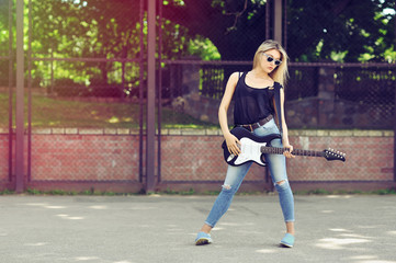 Young beautiful woman with electric guitar wearing sunglasses