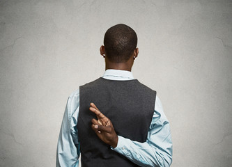 Man crossing fingers behind his back, telling lies in court