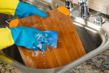 Cleaning Wooden Cutting board inside of Kitchen Sink with sponge