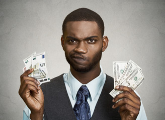 Confused businessman holding dollar, euro bills, grey wall