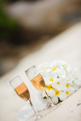 wedding bouquet of frangipani and champagne glasses