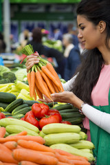 Pretty young woman buying vegetables on the market
