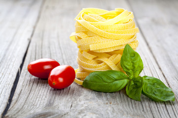 Italian pasta fettuccine nest with  tomatoes and fresh basil lea