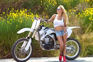 Красивая девушка возле мотоцикла на природе