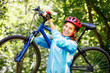 Portrait of young woman with mountain bike on shoulder. - 66984743