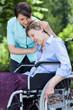 Leinwanddruck Bild - Nurse hugging woman on a wheelchair