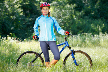 Portrait of happy young woman with mountain bike outdoors.