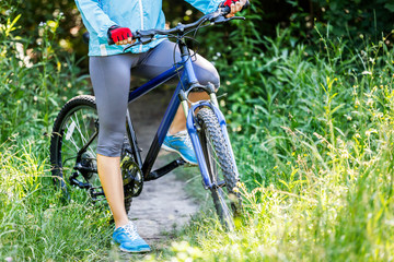 Young woman with mountain bike outdoors.