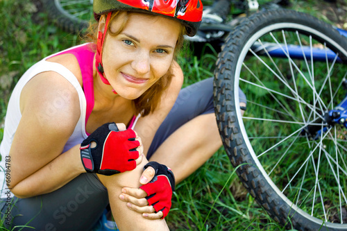 Young woman fell off mountain bike. - 66984783