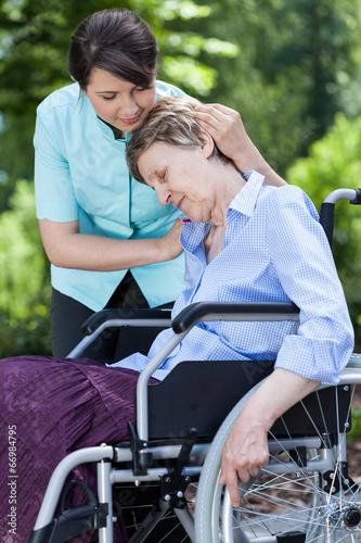 Leinwanddruck Bild Nurse hugging woman on a wheelchair