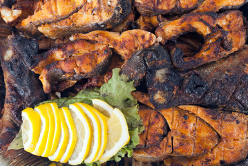 Barbecued fish decorated with lemon wedges.