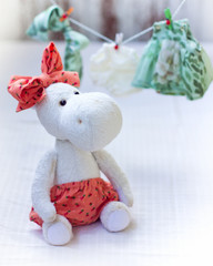 White hippo toy with textile and sewing accessory