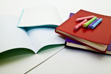 Цветные мелки и тетради на белом фоне