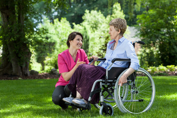 Woman on wheelchair relaxing in garden