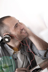 Trendy guy listening to music wiith headset on