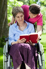 Woman on wheelchair reading book