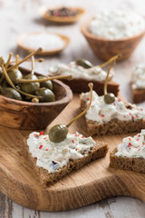 toasts with cheese pate and capers on a wooden board, vertical