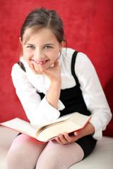 Uśmiechnięta dziewczynka czyta książkę