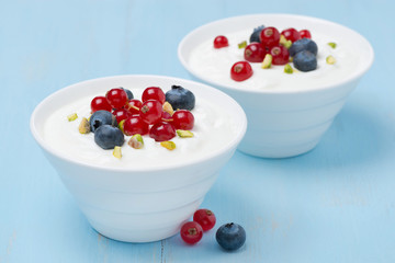 two bowls of fresh sweet yogurt with berries and pistachios