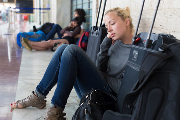 Tired female traveler waiting for departure.